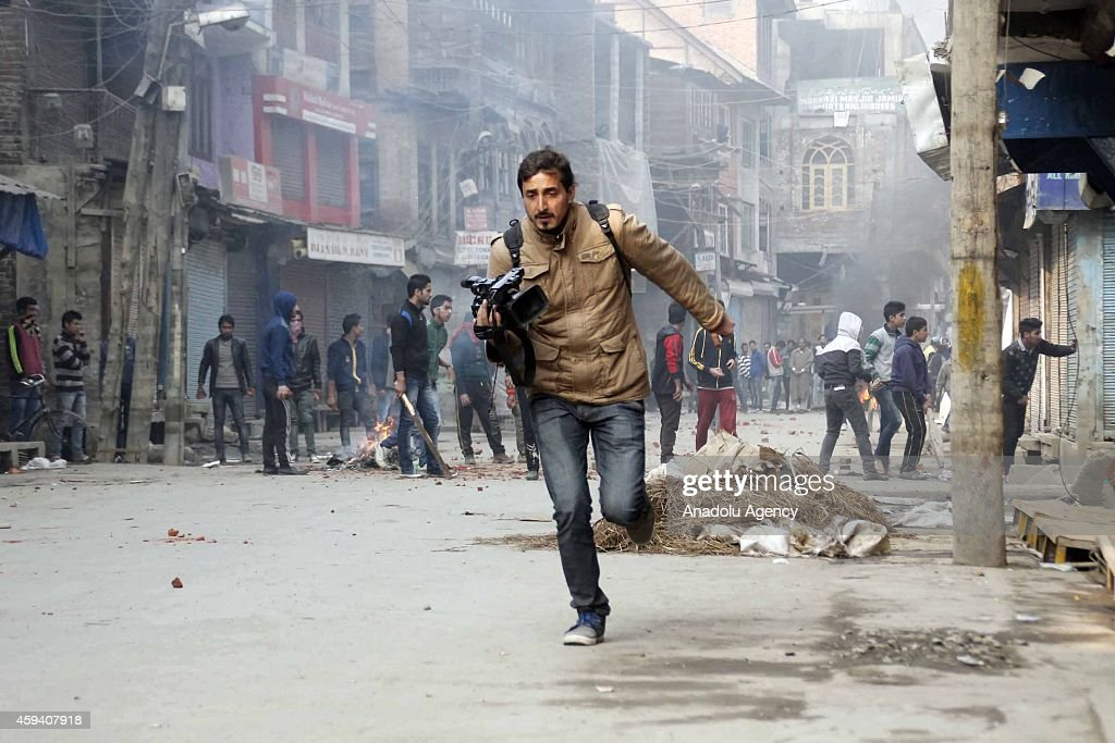A cameraman runs to cover himself during the clashes between young men and police took security measures for Altaf Bukhari, Peoples Democratic Party (PDP) senior leader and party candidate for Amira kadal constituency, in Maisuma district of Srinagar, Kashmir on November 22, 2014.