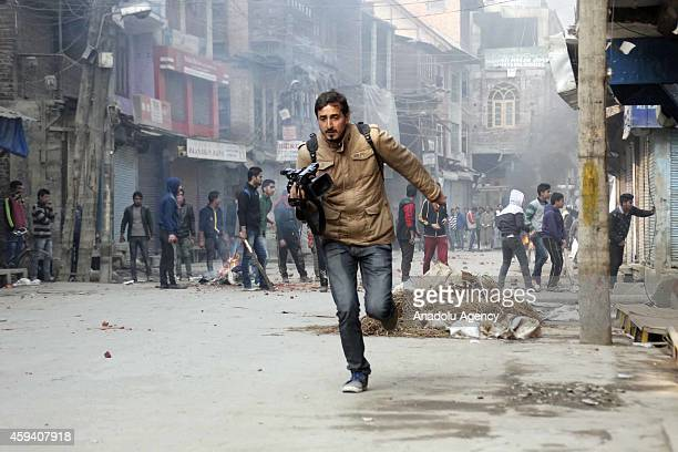 A cameraman runs to cover himself during the clashes between young men and police took security measures for Altaf Bukhari Peoples Democratic Party...