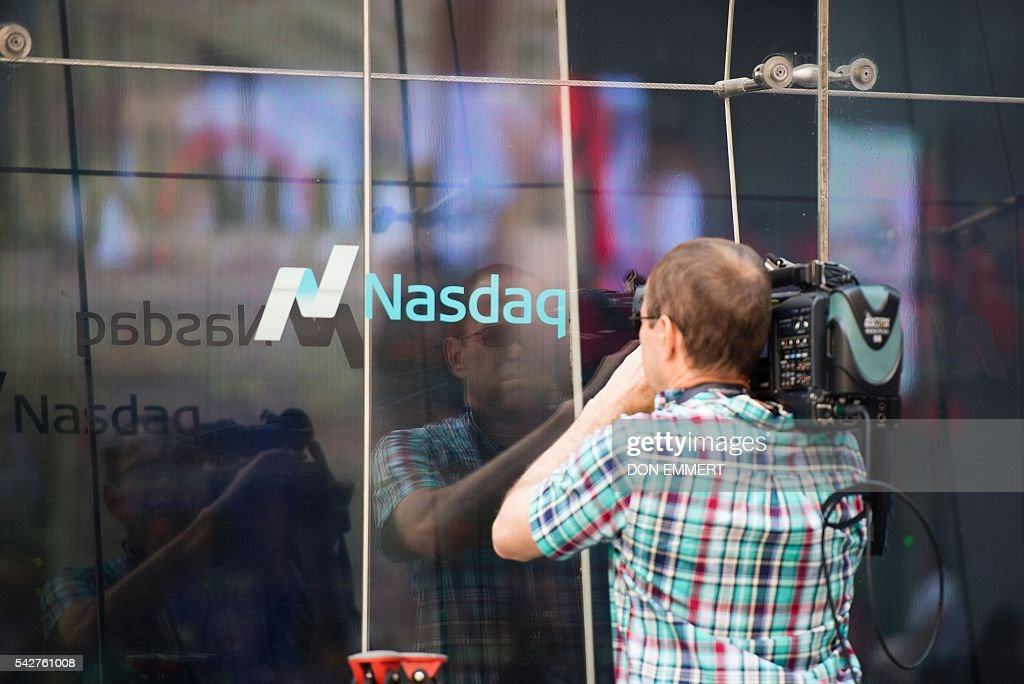 A TV cameraman shoots video through the windows of the Nasdaq offices in Times Square on June 24, 2016 in New York. US stocks tumbled early Friday, with banking equities suffering especially deep losses, joining an international rout after Britain's surprise vote to exit the European Union. The Dow sank more than 500 points shortly after the markets opened at 1330 GMT, but then quickly recovered some of the losses. The selloffs in the US were smaller than in many overseas markets. EMMERT