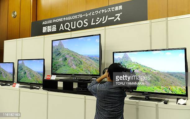 A cameraman takes videos new LCD TV sets of Japan's Sharp Corp during a press conference in Tokyo on June 15 2011 Sharp will put the L5 series LCD...