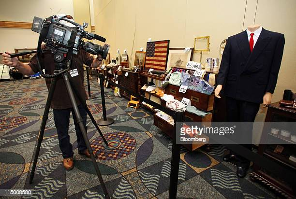 A cameraman tapes clothing from con man Bernard L Madoff's personal wardrobe during a media preview for the final auction of his estate in Miami...