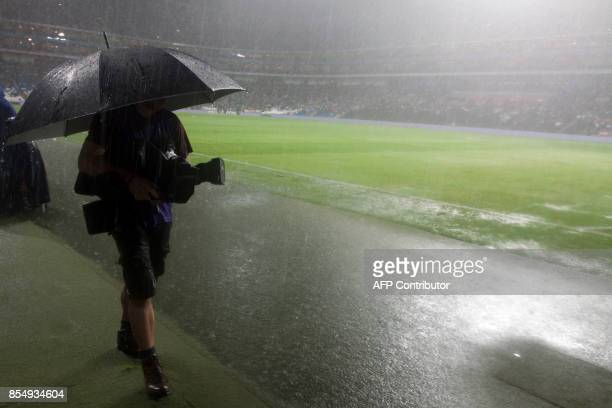 A cameraman walks with umbrella amid a heavy downpour during the rain suspension of the match between Monterrey and Santos at the BBVA Bancomer...