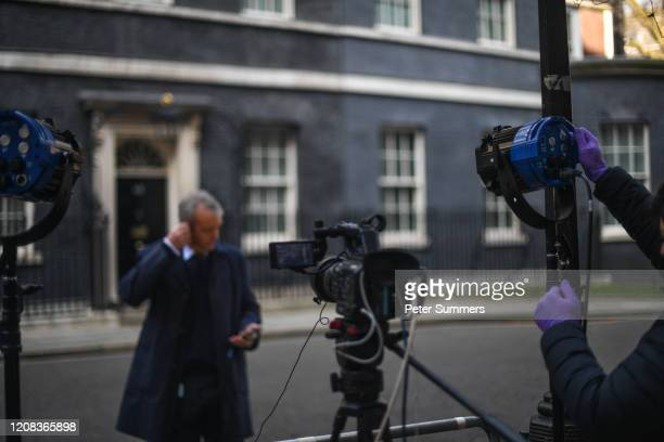 Cameraman wearing protective gloves is seen adjusting a light before a broadcast outside Number 10 Downing Street on March 27, 2020 in London,...