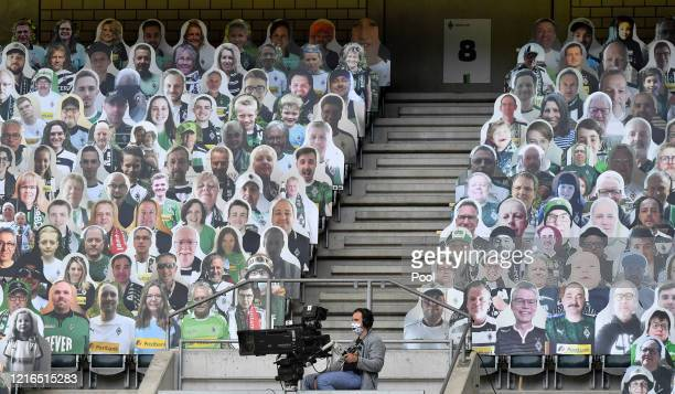 Cameraman wears a face mask seen between cardboards with photos of Moenchengladbach fans displayed on the stands during the Bundesliga match between...