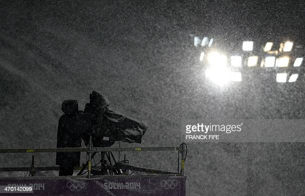 A TV cameraman works under heavy snowfall during the Men's Freestyle Skiing Halfpipe finals at the Rosa Khutor Extreme Park during the Sochi Winter...