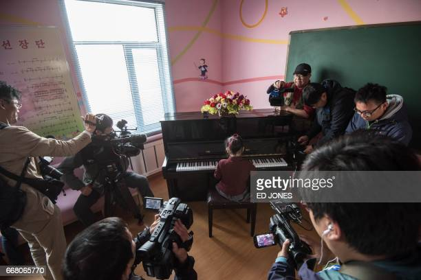 Cameramen film a girl playing the piano during a visit organised for visiting foreign journalists at a school for orphans on the outskirts of...