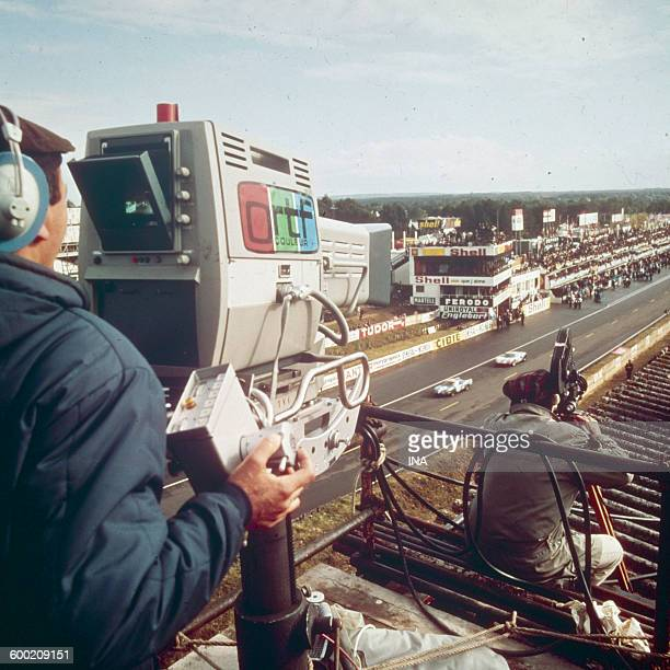 """Cameramen filming the motor racing a """"24 hours of Le Mans""""."""