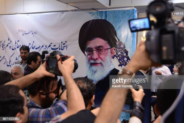 Cameramen stands in front of a banner with a photo of the supreme leader Ayatollah Ali Khamenei while shooting candidates enrolling for the next...