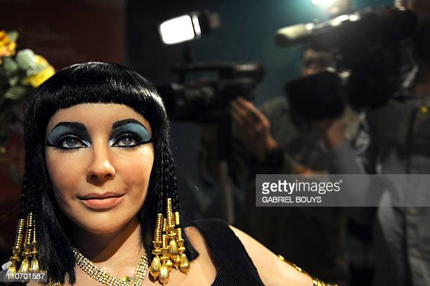 """Cameramen surround the wax figure of Elizabeth Taylor in one of her most famous roles """"Cleopatra"""" at Madame Tussauds in Hollywood California on March..."""