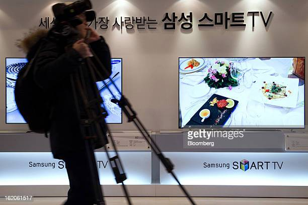 A cameraperson carries equipment past Samsung Electronics Co's F8000 series smart televisions as they are displayed at a media event in Seoul South...