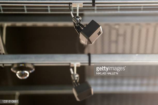 Cameras and technology devices are pictured on the ceiling above the shopping aisles inside Amazon's new Amazon Fresh store in Ealing, west London,...