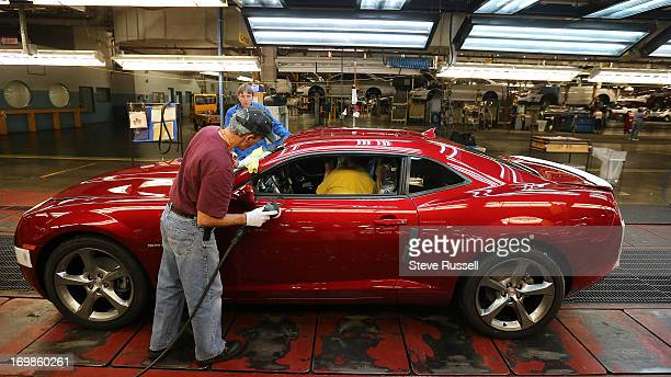 Camero gets a smudge buffed out as it rolls through the final inspection line Cameros are built on the assembly line at the GM Oshawa Assembly Plant...