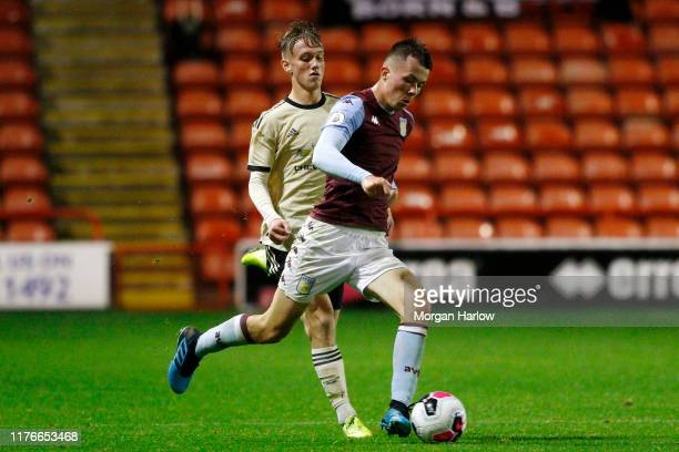 Cameron Archer of Aston Villa runs with the ball with pressure from Ethan Galbraith of Man United during the Premier League 2 match between Aston...