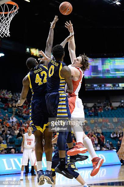 Cameron Bairstow of the New Mexico Lobos puts up a shot against Chris Otule and Jamil Wilson of the Marquette Golden Eagles during their game at the...