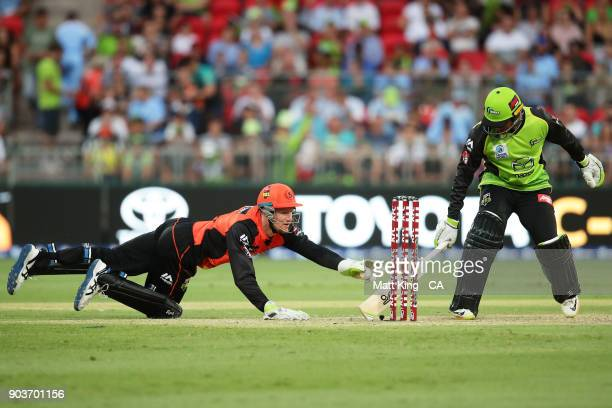 Cameron Bancroft of the Scorchers attempts to run out Usman Khawaja of the Thunder during the Big Bash League match between the Sydney Thunder and...