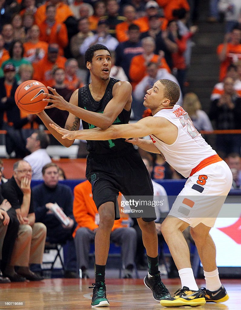 Cameron Biedscheid #1 of the Notre Dame Fighting Irish attempts to pass the ball against Brandon Triche #20 of the Syracuse Orange during the game at the Carrier Dome on February 4, 2013 in Syracuse, New York.