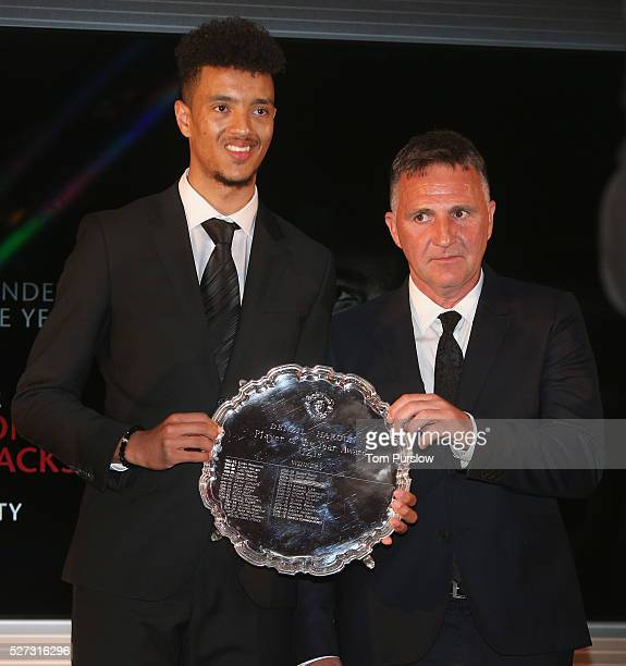 Cameron Borthwick-Jackson of Manchester United is presented with the Denzil Haroun Reserve team Player of the Season award by U21s team manager...