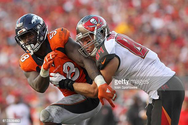 Cameron Brate of the Buccaneers attempts to block and then he wraps up Von Miller of the Broncos during the regular season game between the Denver...