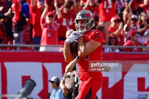 Cameron Brate of the Tampa Bay Buccaneers scores on a 3yard reception thrown by Jameis Winston during the second quarter of a football game against...
