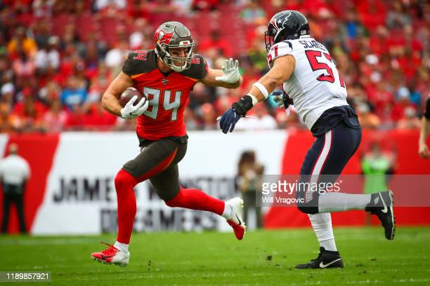 Cameron Brate of the Tampa Bay Buccaneers stiff arms Brennan Scarlett of the Houston Texans on a run during the first half on December 21, 2019 at...