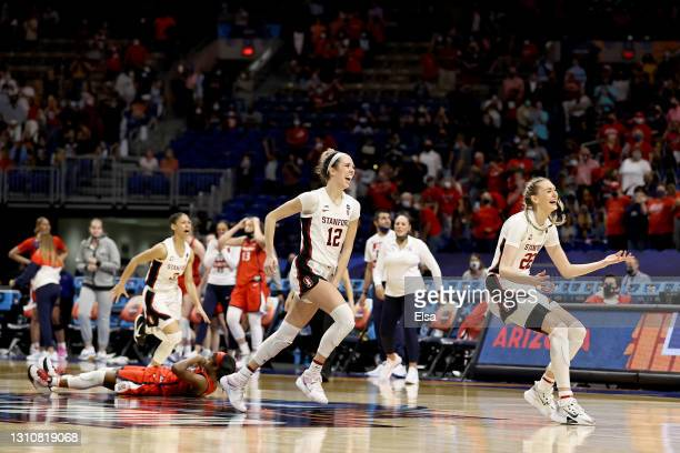 Cameron Brink of the Stanford Cardinal and Lexie Hull of the Stanford Cardinal celebrate a win as Aari McDonald of the Arizona Wildcats lays on the...