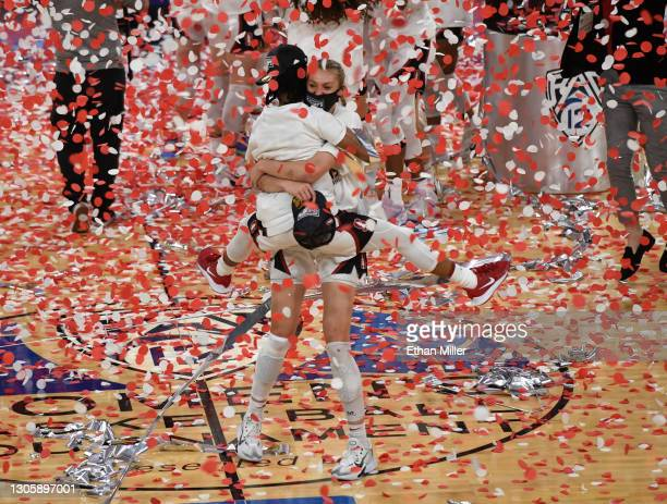 Cameron Brink of the Stanford Cardinal picks up teammate Kiana Williams as they celebrate their 75-55 victory over the UCLA Bruins to win the...