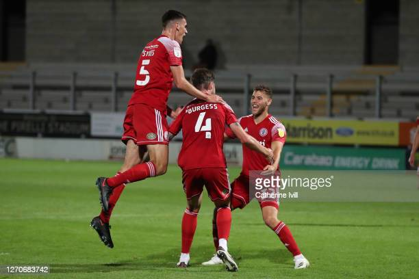 Cameron Burgess of Accrington Stanley celebrates with Ross Sykes and Dion Charles during the Carabao Cup First Round match between Burton Albion and...