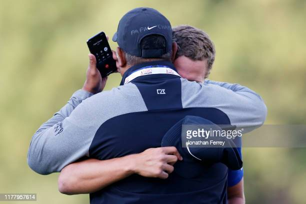 Cameron Champ hugs his father, Jeff Champ, while on the phone with his grandfather after winning the final round of the Safeway Open at the Silverado...