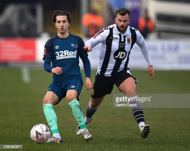 Cameron Cresswell of Derby County is challenged by Andy Halls of Chorley FC during the FA Cup Third Round match between Chorley and Derby County at...