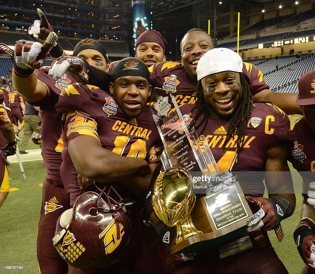 Cameron Davis #19 and Jahleel Addae #4 of the Central Michigan University Chippewas hold the Little Caesars Pizza Bowl Championship Trophy along with teammates after the victory against the Western Kentucky University Hilltoppers at Ford Field on December 26, 2012 in Detroit, Michigan. The Chippewas defeated the Hilltoppers 24-21.