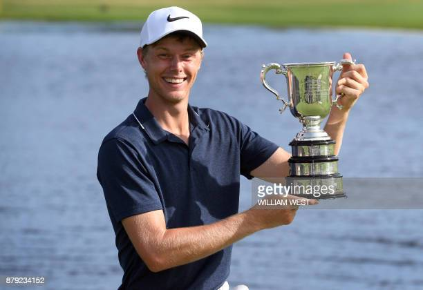 Cameron Davis of Australia holds up the trophy after winning the Australian Open played at the Australian Golf Club course in Sydney on November 26...