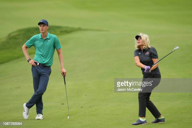 Cameron Davis of Australia watches KerriAnn Kennerley plays a chip shot to the 11th green ahead of the 2018 Australian Golf Open at The Lakes Golf...
