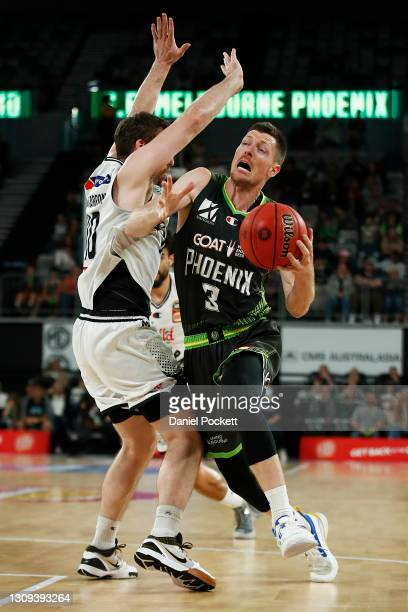 Cameron Gliddon of the Phoenix drives to the basket under pressure from Mitch McCarron of United during the round 11 NBL match between Melbourne...