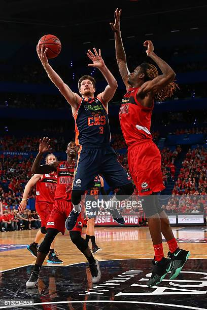 Cameron Gliddon of the Taipans lays up against Jameel McKay of the Wildcats during the round one NBL match between the Perth Wildcats and the Cairns...
