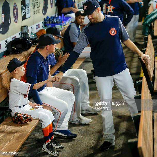 Cameron Gooch sits on the bench with Will Harris as he gets fist bump from Collin McHugh at Minute Maid Park on August 17 2017 in Houston Texas...