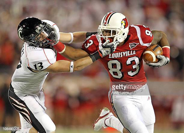 Cameron Graham of the Louisville Cardinals runs with the ball while defended by Cody Kater of the Cincinnati Bearcats during the game at Papa John's...