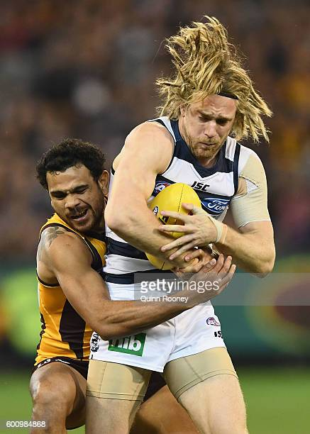 Cameron Guthrie of the Cats is tackled by Cyril Rioli of the Hawks during the 2nd AFL Qualifying Final match between the Geelong Cats and the...