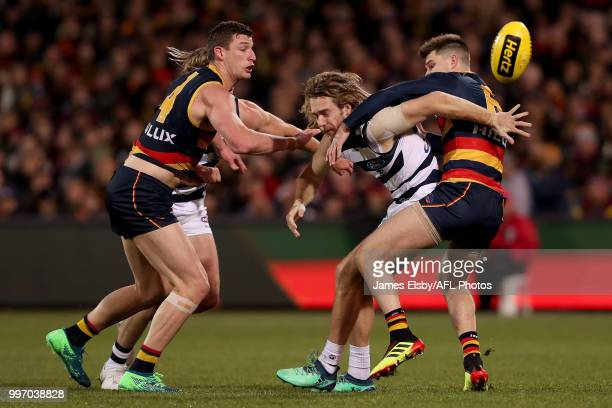 Cameron Guthrie of the Cats is tackled by Josh Jenkins and Bryce Gibbs of the Crows during the 2018 AFL round 17 match between the Adelaide Crows and...