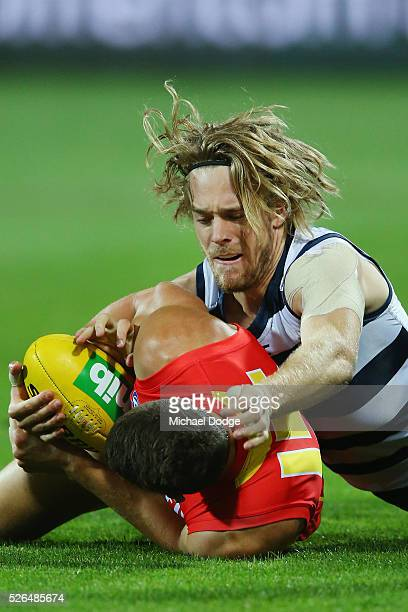 Cameron Guthrie of the Cats tackles Daniel Currie of the Suns during the round six AFL match between the Geelong Cats and the Gold Coast Suns at...