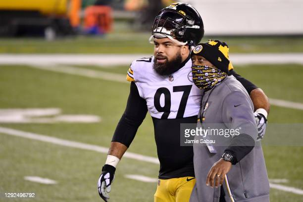 Cameron Heyward of the Pittsburgh Steelers and head coach Mike Tomlin walk along the field prior to taking on the Cincinnati Bengals at Paul Brown...