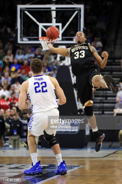 Cameron Jackson of the Wofford Terriers reaches for the ball against Reid Travis of the Kentucky Wildcats during the first half of the game in the...