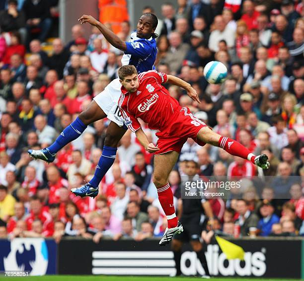 Cameron Jerome of Birmingham City jumps with Steven Gerrard of Liverpool during the Barclays Premier League match between Liverpool and Birmingham...