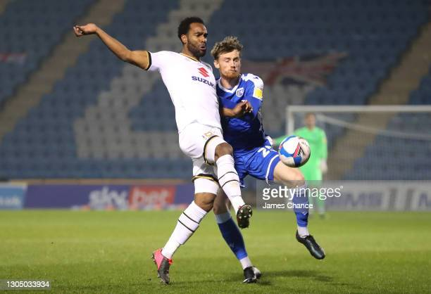 Cameron Jerome of Milton Keynes Dons is challenged by Robbie Cundy of Gillingham FC during the Sky Bet League One match between Gillingham and Milton...