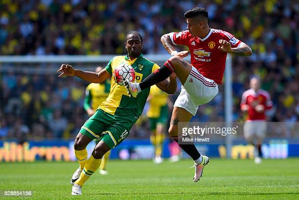 Cameron Jerome of Norwich City and Marcos Roja of Manchester United compete for the ball during the Barclays Premier League match between Norwich...