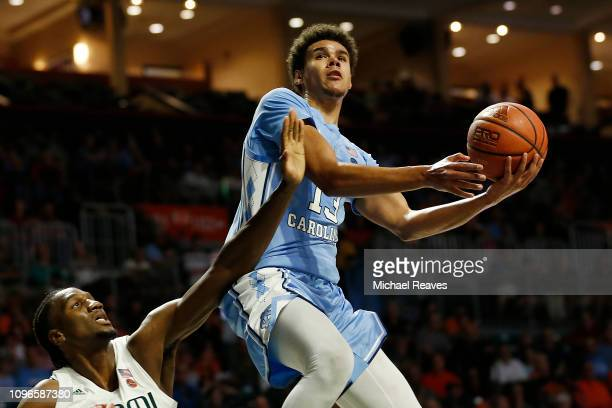 Cameron Johnson of the North Carolina Tar Heels attempts a layup over Ebuka Izundu of the Miami Hurricanes during the first half at Watsco Center on...