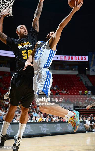 Cameron Jones of the Golden State Warriors goes to the basket against Robert Sacre of the Los Angeles Lakers during NBA Summer League game between...