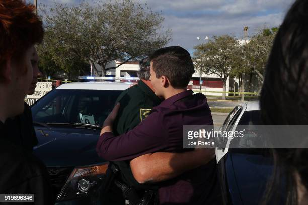 Cameron Kasky jr a student at Marjory Stoneman Douglas High School hugs Broward County Sheriff officer Brad Griesinger as he guards the front gate of...