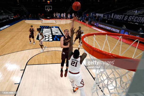 Cameron Krutwig of the Loyola Chicago Ramblers shoots the ball over Kofi Cockburn of the Illinois Fighting Illini during the second half in the...