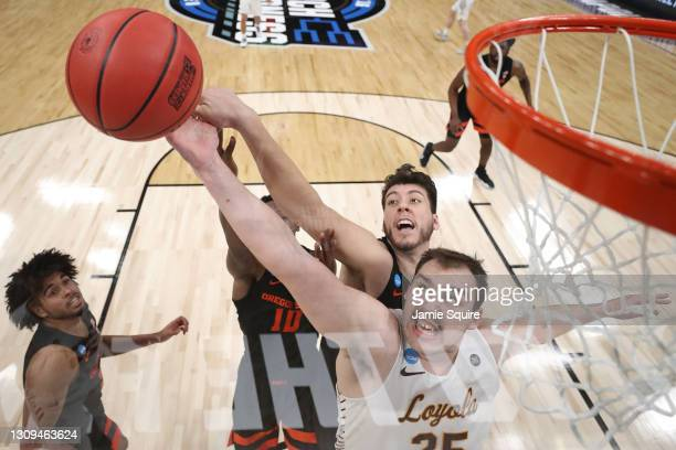 Cameron Krutwig of the Loyola-Chicago Ramblers battles for the ball with Warith Alatishe of the Oregon State Beavers and Roman Silva during the first...
