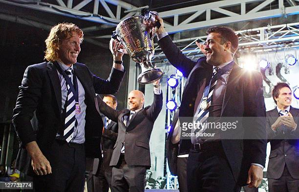 Cameron Ling captain and Chris Scott coach of the Geelong Football Club arrive with the Premiership Cup after the 2011 AFL Grand Final match between...